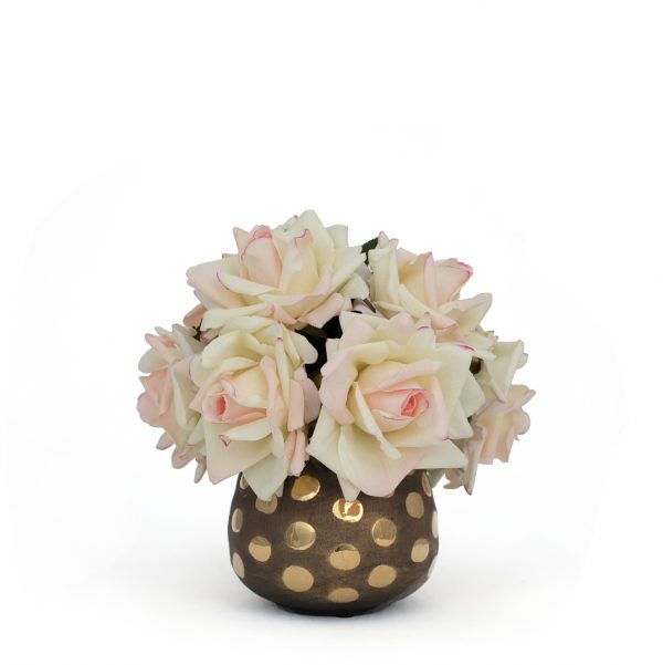 Artificial blush rose arrangement in ceramic bronze and gold polka dotted vessel on white background