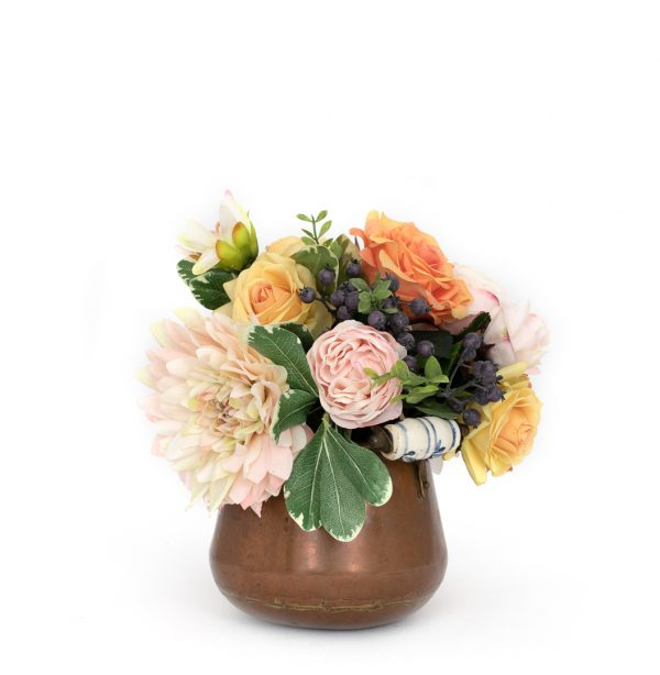 Faux floral arrangement of dahlias and roses in vintage copper pot on white background