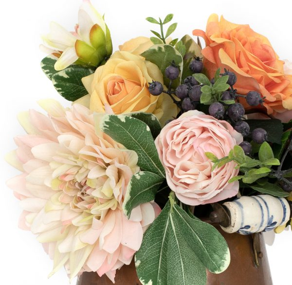 Closeup of faux floral arrangement of dahlias and roses in vintage copper pot on white background