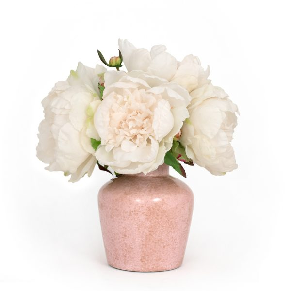 Artificial blush peonies in pink ceramic vase on white background