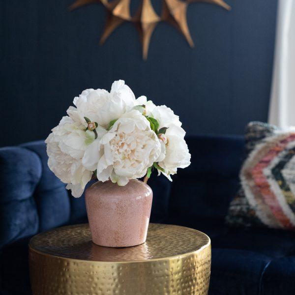 Artificial blush peonies and pink ceramic vase in living room