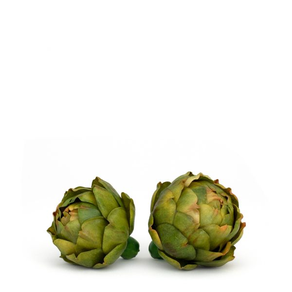 Side-by-side small and medium faux green artichokes on white background