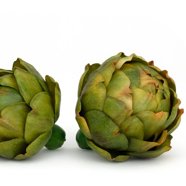 Closeup of side-by-side small and medium faux green artichokes on white background