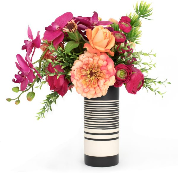 Tropical style artificial floral arrangement in a modern black and white striped vase on white background