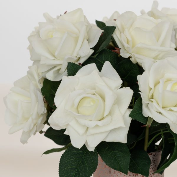 Closeup of one dozen real touch artificial white roses in pink vase on soft background